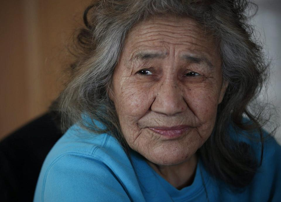 Close-up of an Indigenous woman with grey hair in a blue shirt