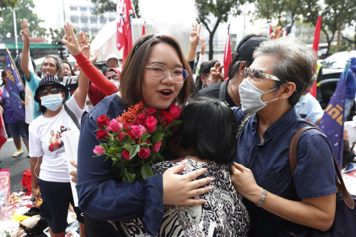 A pro-democracy activist, Panusaya Sithijirawattanakul, front left, receives a flower from her supporter as she arrived at the Attorney General office in Bangkok, Thailand, Monday, March 8, 2021. Prosecutors in Thailand charged 18 pro-democracy activists with sedition on Monday, while lodging additional charges of insulting the monarchy against three of them. (AP Photo/Sakchai Lalit)
