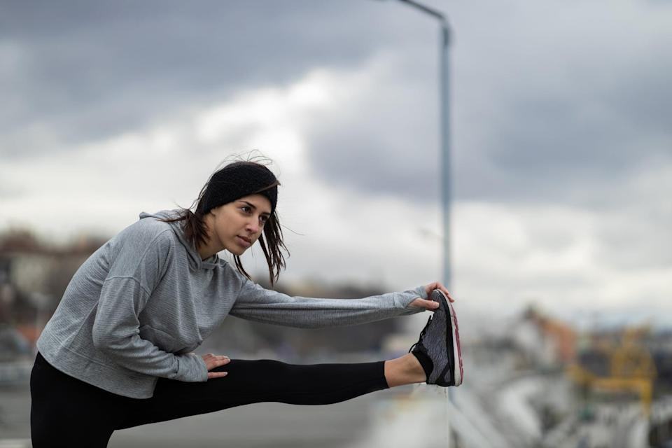 Handsome young Caucasian sportswoman doing warm up exercises outdoors on a cold weather day in the city