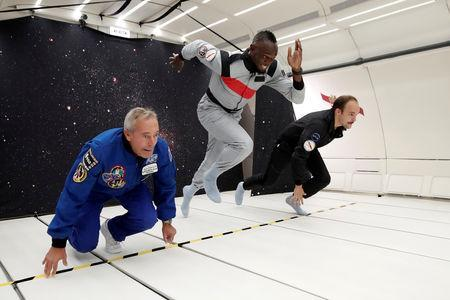 """Retired sprinter Usain Bolt, French astronaut Jean-Francois Clervoy, CEO of Novespace, and French Interior designer Octave de Gaulle who designed a bottle of """"Mumm Grand Cordon Stellar"""" enjoy zero gravity conditions during a flight in a specially modified Airbus Zero-G plane above Reims, France, September 12, 2018. REUTERS/Benoit Tessier"""