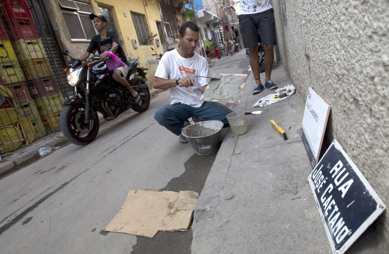 In this Dec. 28, 2012 photo, a worker prepares cement that will be used to hang a street sign at the Mare shantytown in Rio de Janeiro, Brazil. The city's densest neighborhoods, its favelas, or shantytowns blanket entire hillsides, providing most of the city's affordable housing. Now, those communities are being charted after decades of informality, each route and alley outlined and their names researched. Being left off the map had meant whole communities were unable to receive mail at home. It had also blocked people from giving required information on job applications, getting a bank account or telling the police or fire department where to go in an emergency call. (AP Photo/Silvia Izquierdo)