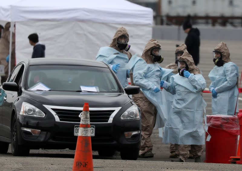 Members of the Colorado Air National Guard test people who suspect they are infected with coronavirus disease (COVID-19), at a drive-thru testing station, in Denver