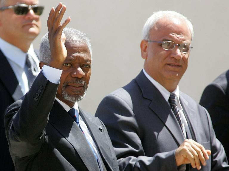 In this file photo taken on August 30, 2006, then UN Secretary General Kofi Annan (L) and Palestinian chief negotiator Saeb Erekat wave as Annan arrives at Palestinian Authority headquarters in the West Bank city of Ramallah