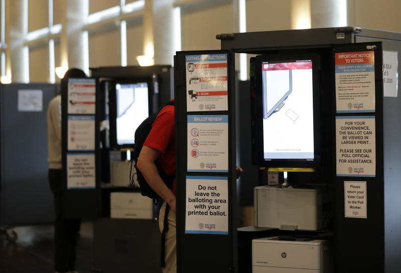 People vote at voting booths in the Georgia's primary election at Park Tavern on Tuesday, June 9, 2020, in Atlanta. (AP Photo/Brynn Anderson)