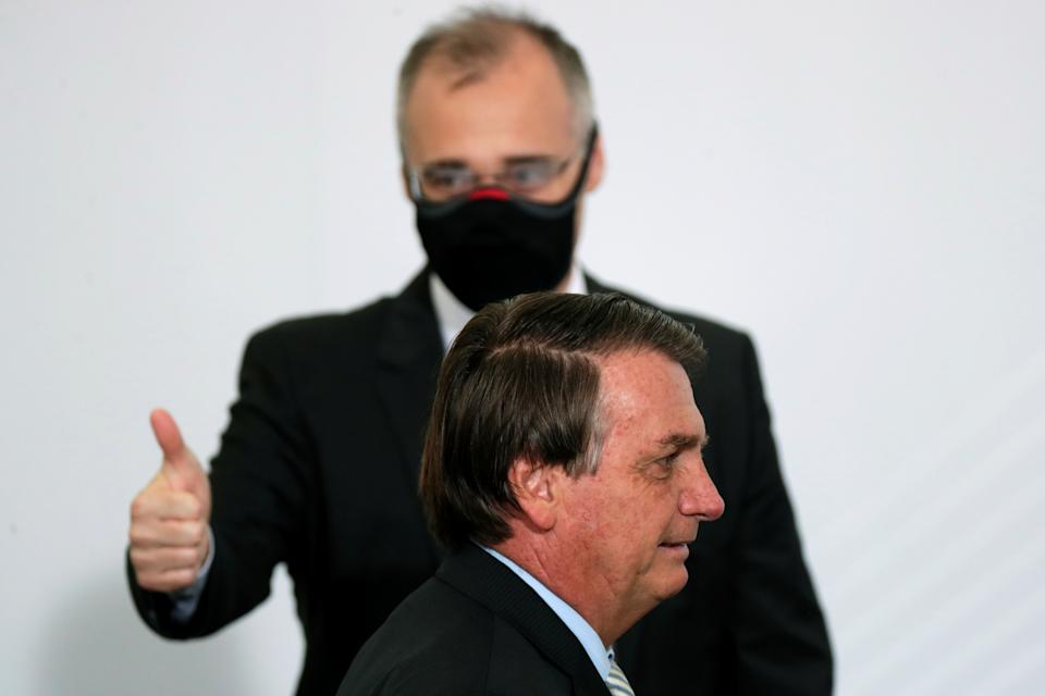 Brazil's Justice Minister Andre Luiz de Almeida Mendonca, wearing a protective mask, gestures next to Brazil's President Jair Bolsonaro after the opening of the forum 'Control in the Fight against Corruption 2020' at the Planalto Palace in Brasilia, Brazil, December 9, 2020. REUTERS/Ueslei Marcelino