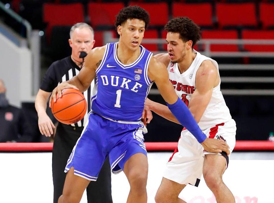 Duke's Jalen Johnson (1) looks for space as N.C. State's Jericole Hellems (4) defends during the first half of N.C. State's game against Duke at PNC Arena in Raleigh, N.C., Saturday, February 13, 2021.