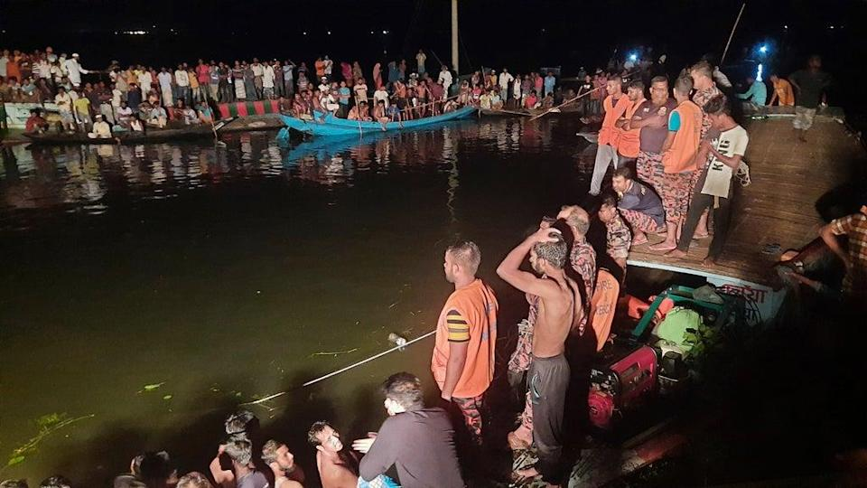 People watch rescue workers after a passenger boat sank in Brahmanbaria district, Bangladesh (AP)