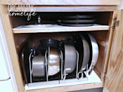 """<p>To keep you little piggies safe, use organizers that let you stack items on their sides. Then, all you have to do when you need a pan is pull it out without having to worry about causing a kitchen disaster.</p><p><em><a href=""""http://www.organizinghomelife.com/diy-knock-off-organization-for-pots-pans-how-to-organize-your-kitchen-frugally-day-26/"""" rel=""""nofollow noopener"""" target=""""_blank"""" data-ylk=""""slk:See more at Organizing Home Life »"""" class=""""link rapid-noclick-resp"""">See more at Organizing Home Life »</a></em></p><p><strong>What you'll need: </strong><span class=""""redactor-invisible-space"""">cabinet organizers, $18, <a href=""""https://www.amazon.com/Organized-Living-Sort-Divider-White/dp/B00525W1BY/?tag=syn-yahoo-20&ascsubtag=%5Bartid%7C10063.g.36078080%5Bsrc%7Cyahoo-us"""" rel=""""nofollow noopener"""" target=""""_blank"""" data-ylk=""""slk:amazon.com"""" class=""""link rapid-noclick-resp"""">amazon.com</a></span><br></p>"""