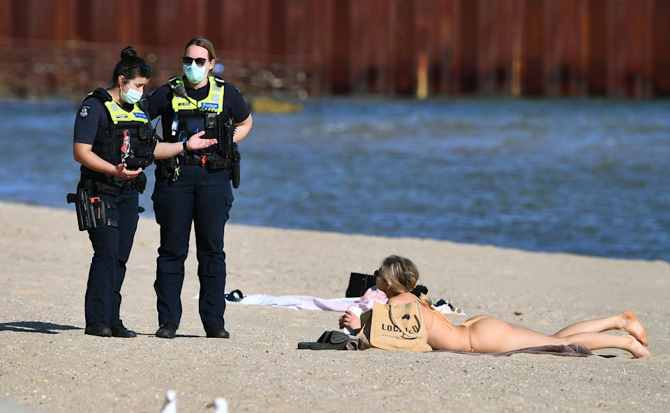Police speak to a woman enjoying the unusually warm spring weather at St Kilda Beach in Melbourne earlier this month. Source: Getty