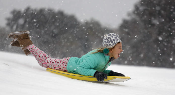 <p>Finley Bork, 7, uses a boogie board, typically used on the beach, for sledding down a hill on a golf course at the Isle of Palms, S.C., Wednesday, Jan. 3, 2018. (Photo: Mic Smith/AP) </p>