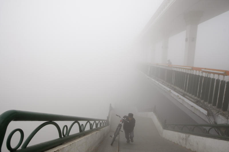 A man pushes a bike onto a bridge during a day of heavy pollution in Harbin in northeast China's Heilongjiang province Monday Oct. 21, 2013. Visibility shrank to less than half a football field and small-particle pollution soared to a record 40 times higher than an international safety standard in the northern Chinese city as the region entered its high-smog season. (AP Photo) CHINA OUT