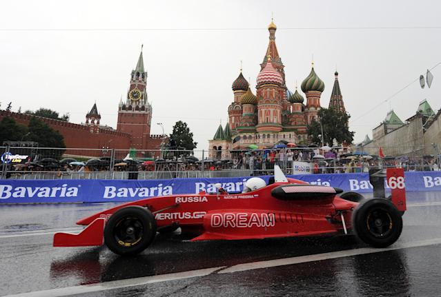 """Russia's racing driver Natalie Freidina drives past St. Basils cathedral during the """"Moscow City Racing"""" show on July 17, 2011 in central Moscow. AFP PHOTO / NATALIA KOLESNIKOVA (Photo credit should read NATALIA KOLESNIKOVA/AFP/Getty Images)"""