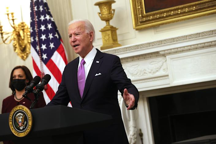 WASHINGTON, DC - JANUARY 21: U.S. President Joe Biden speaks as Vice President Kamala Harris looks on during an event at the State Dining Room of the White House January 21, 2021 in Washington, DC. President Biden delivered remarks on his administration's COVID-19 response, and signed executive orders and other presidential actions. (Photo by Alex Wong/Getty Images)