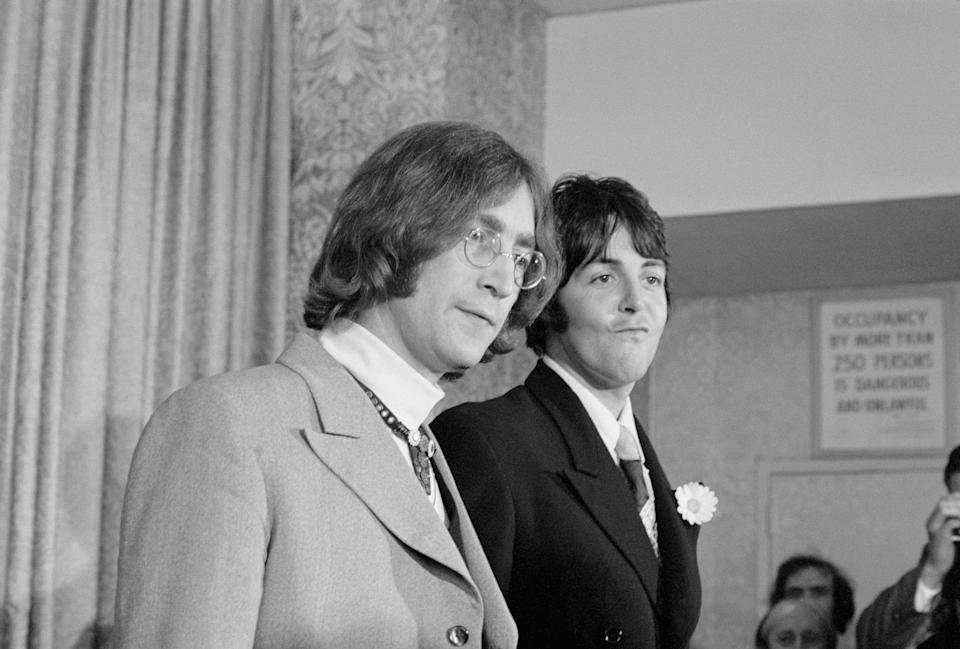 "(Original Caption) Beatle business...Beatles John Lennon (left) and Paul McCartney face the press here, May 14th, and announce the establishment of an organization to serve as a catchall of the entertainment business. The British quartet has transformed its Beatles Ltd. into Apple Corps, Ltd., which has purchased, for $1.5 million an 18th century building on Savile Row to serve as headquarters for projects in films, electronics, recordings and merchandising. In their usual glib way, the two gave vague answers to newsmen's questions. ""We don't know anything about business. We've hired people for that,"" was one example."