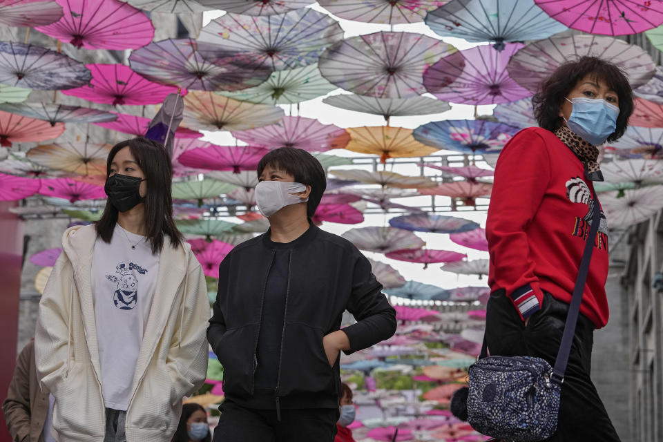 Visitors wearing face masks walk under colorful umbrellas on display along a hutong alley near Qianmen Avenue, a popular tourist spot in Beijing, Thursday, Oct. 14, 2021. (AP Photo/Andy Wong)