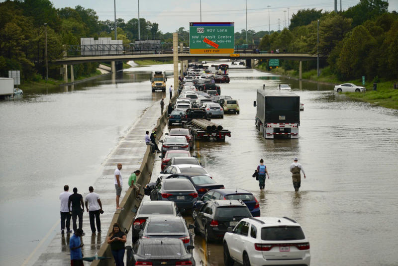 People wait outside of their stranded vehicles along Interstate 10 westbound at T.C Jester, Sept. 19, 2019. The freeway is closed because of high water east bound on the freeway. (Photo: Mark Mulligan/Houston Chronicle via AP)