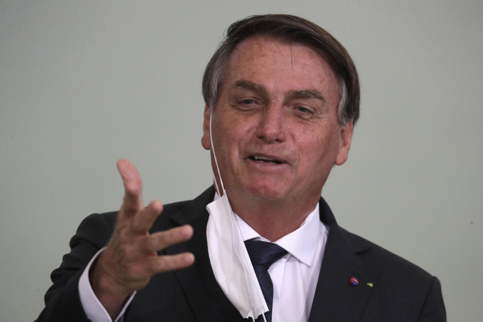 "Brazil's President Jair Bolsonaro, his protective face mask hanging from his ear, speaks during a ceremony launching the housing program ""Green and Yellow House,"" at the Planalto presidential palace in Brasilia, Brazil, Tuesday, Aug. 25, 2020, amid the new coronavirus pandemic. (AP Photo/Eraldo Peres)"
