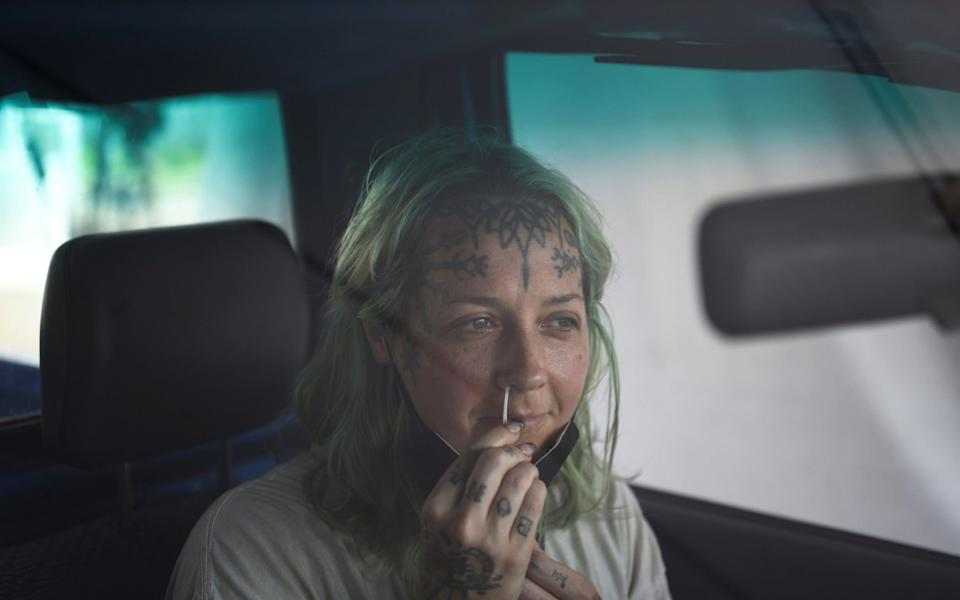 A woman uses a nasal swab to provide a sample as cases surge across New Orleans in the US - Callaghan O'Hare/Reuters