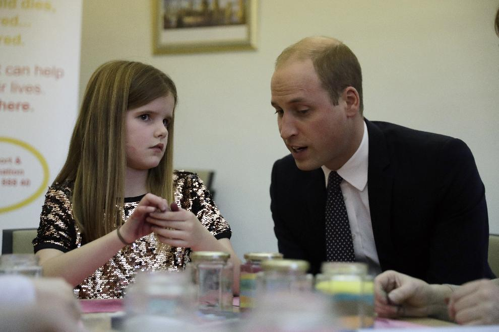 Britain's Prince William speaks with Aoife, 9, during his visit to a Child Bereavement UK Centre in Stratford in east London, Wednesday, Jan. 11, 2017. Prince William has been the royal patron of the Child Bereavement UK organisation since 2009. It supports families and educates professionals when a baby or child of any age dies or is dying, or when a child is facing bereavement. (AP Photo/Matt Dunham, Pool)