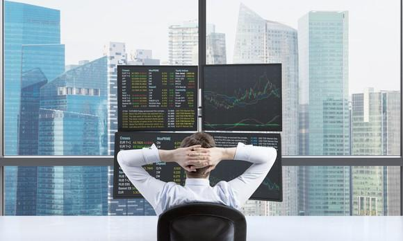 Person in front of four-monitor stock trading setup with window overlooking urban skyline.