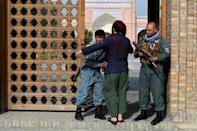 An Afghan security personnel frisks devotees at the entrance of a mosque during the Eid al-Adha prayers in Kabul
