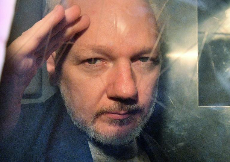 Julian Assange gestures from the window of a prison van in May 2019 after a court in London sentenced him to 50 weeks in prison for breaching his bail conditions in 2012
