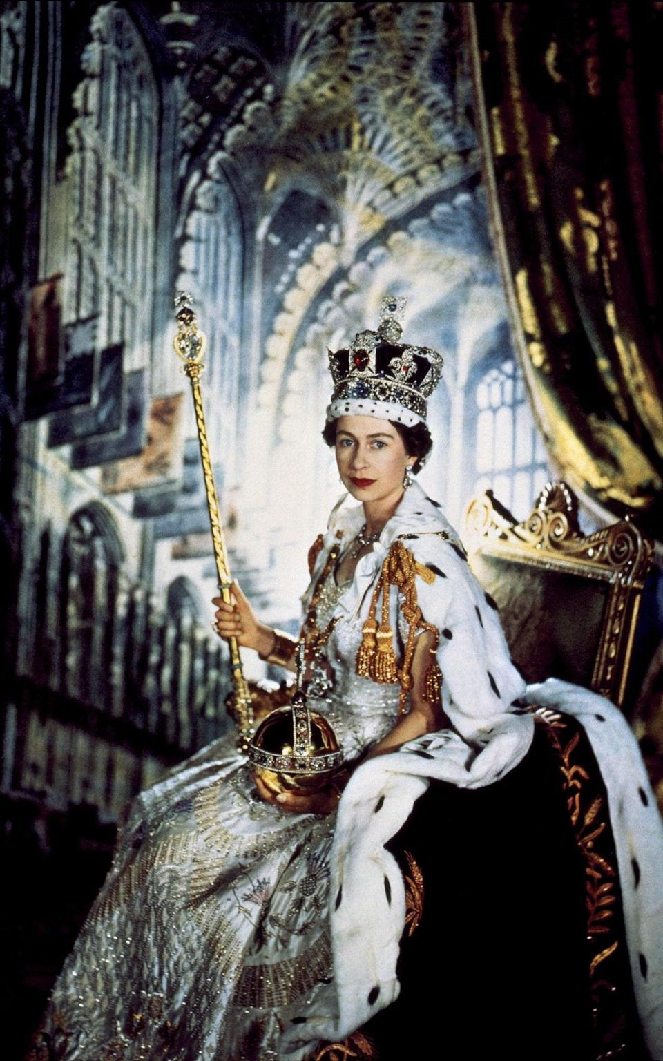 Queen Elizabeth II (b.1926) in her Coronation robes, with crown, sceptre & orb, with studio backdrop of Westminster Abbey; by Sir Cecil Beaton (1904 - 80) English; 1953. C-Type colour print. - PA