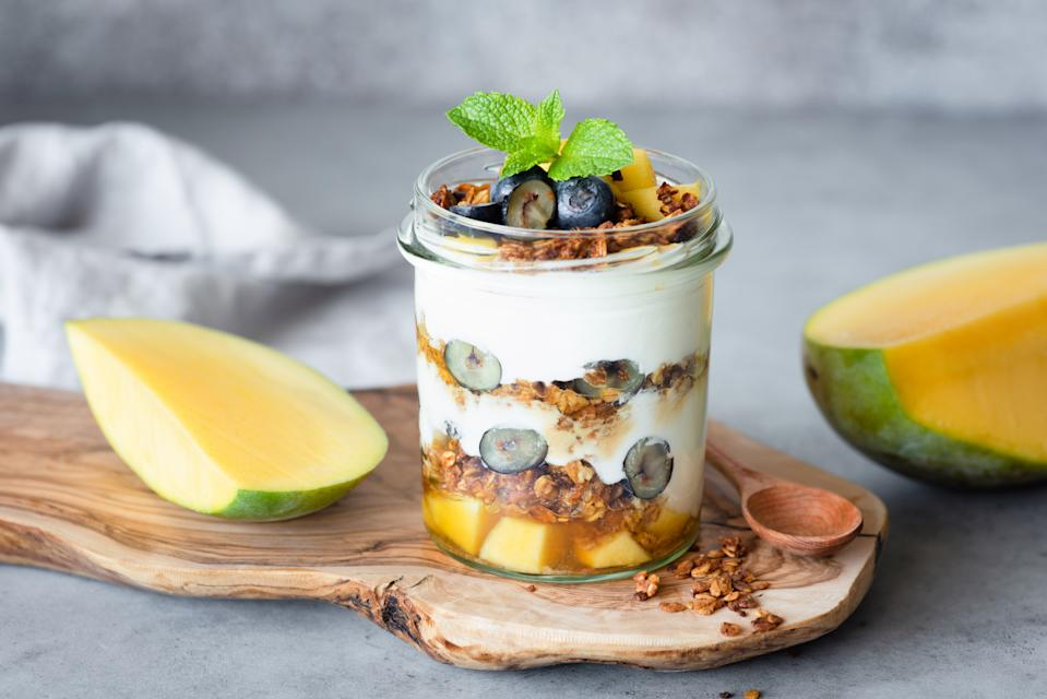 Breakfast yogurt parfait with granola, mango, berries in jar on concrete background. Concept of healthy lifestyle, healthy eating, dieting, yoga and fitness menu