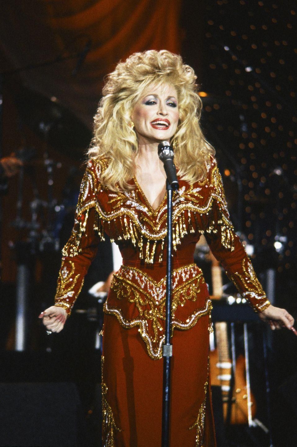 """<p>Dolly dazzles here in a brick red dress embellished with a variety of golden accents for a performance on """"The Johnny Carson Show."""" She plays up the country-fied style of the 1970s in a more modern way for the '80s. </p>"""