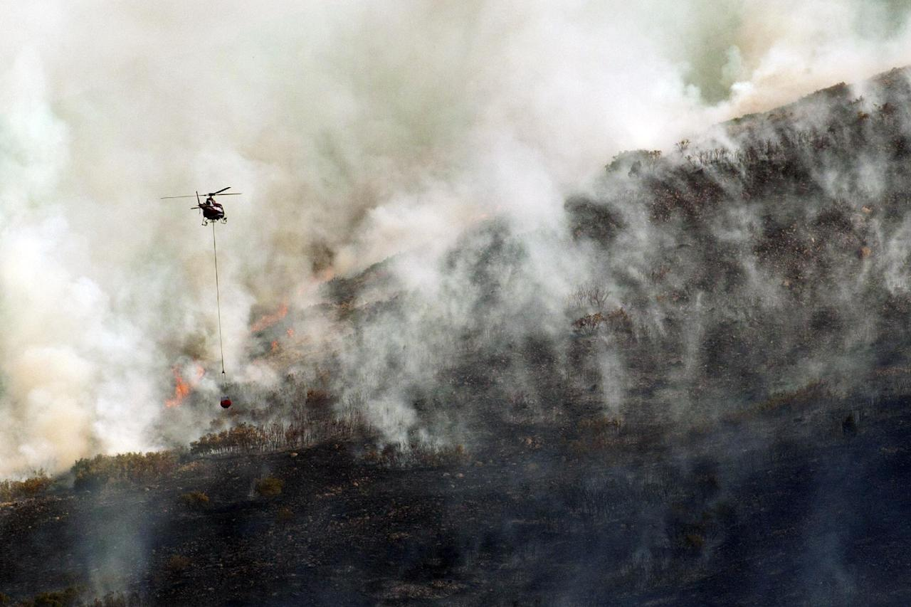 Helicopters work to help put out the Rose Crest Fire around Herriman, Utah Friday June 29, 2012. Officials say the fire has burned at least two homes and threatens 200 more in the foothills around Herriman, southwest of Salt Lake City. (AP Photo/The Salt Lake Tribune, Chris Detrick)