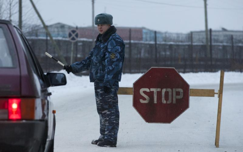 A prison service officer stops a car on the road at the prison where Mikhail Khodorkovsky was kept in Segezha, near Petrozavodsk, Russia, Friday, Dec. 20, 2013. Russia's once richest man Mikhail Khodorkovsky, the arch rival of President Vladimir Putin, has been released from prison after a decade behind bars, his spokeswoman told the Associated Press on Friday. Khodorkovsky spent 10 years in prison on politically tinted charges of tax evasion and embezzlement. (AP Photo/Ivan Sekretarev)