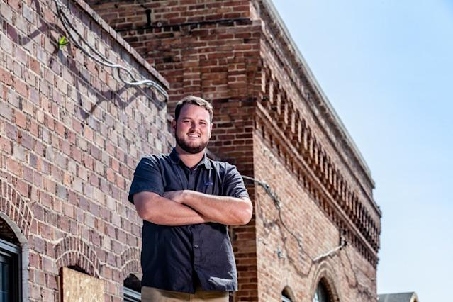 """<div class=""""caption""""> Mitchell stands outside a former steam plant renovated into the Pinehurst Brewing Company,. </div> <cite class=""""credit"""">John Gessner/Pinehurst Resort</cite>"""