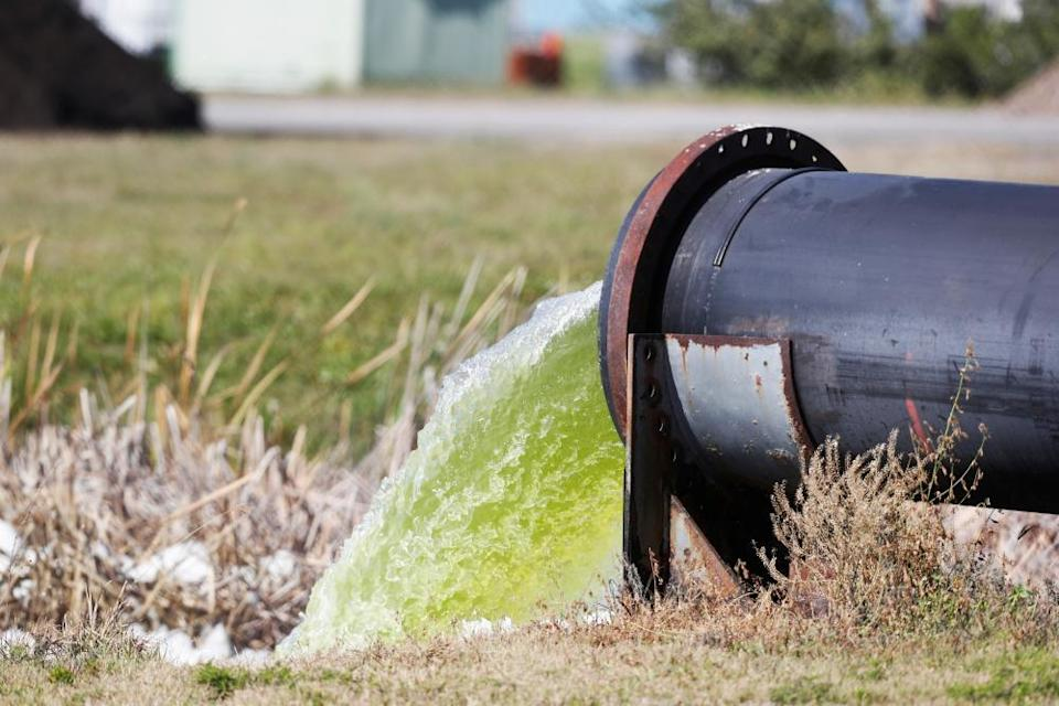 Effluent spews from a pipe into a ditch at Port Manatee, where a breach in a nearby wastewater reservoir on the site of a defunct phosphate plant forced an evacuation order.