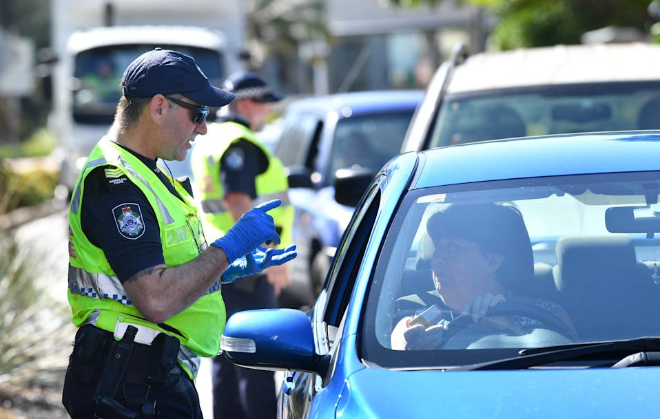 Police are seen stopping cars at a check point on the Queensland and New South Wales border on Griffith Street in Coolangatta at the Gold Coast. Source: AAP