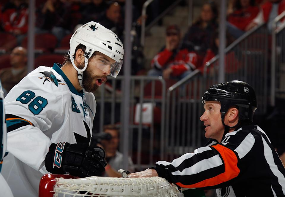 NEWARK, NJ - OCTOBER 18: Brent Burns #88 of the San Jose Sharks argues a second period call with referee Kelly Sutherland #11 during the game against the New Jersey Devils at the Prudential Center on October 18, 2014 in Newark, New Jersey.  (Photo by Bruce Bennett/Getty Images)