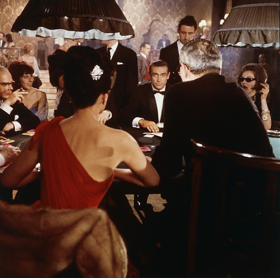 Scottish actor Sean Connery (center) as fictional secret agent James Bond sits at a casino card table in a scene from the film 'Dr. No,' directed by Terence Young, 1962. British actress Eunice Gayson sits with her back to the camera in a red, off the shoulder dress. (Photo by MGM Studios/Courtesy of Getty Images)