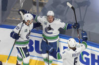 Vancouver Canucks' Bo Horvat (53), Troy Stecher (51) and Brock Boeser (6) celebrate a goal against the St. Louis Blues during the third period in Game 1 of an NHL hockey Stanley Cup first-round playoff series, Wednesday, Aug. 12, 2020, in Edmonton, Alberta. (Jason Franson/The Canadian Press via AP)
