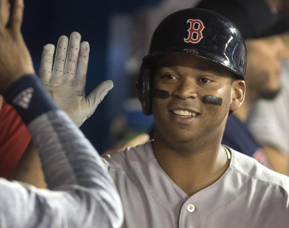 Boston Red Sox's Rafael Devers is congratulated for his two-run home run against the Toronto Blue Jays during the eighth inning of a baseball game Tuesday, July 2, 2019, in Toronto. (Fred Thornhill/The Canadian Press via AP)