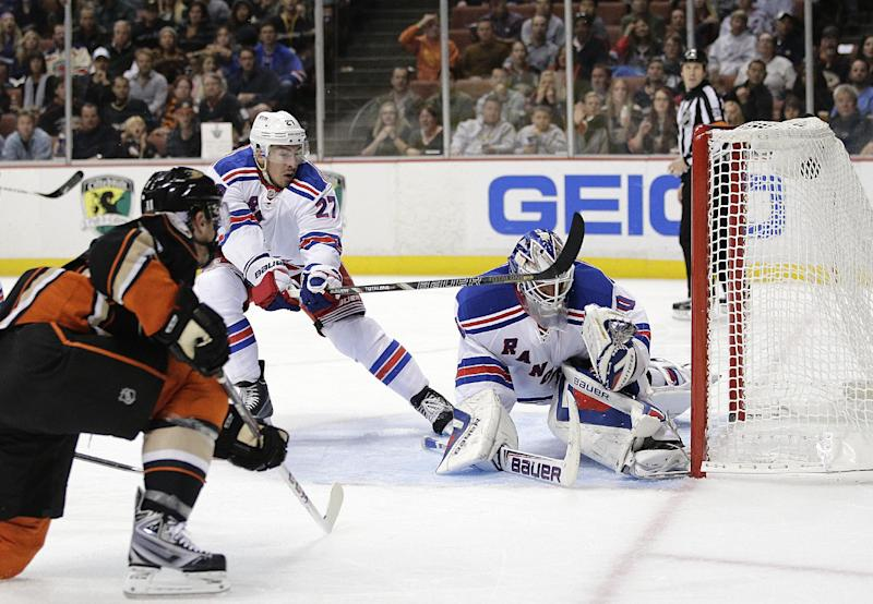 Anaheim Ducks' Saku Koivu, left, of Finland, scores against New York Rangers goalie Henrik Lundqvist, right, of Sweden, as Rangers' Ryan McDonagh, center, helps defend during the second period of an NHL hockey game Thursday, Oct. 10, 2013, in Anaheim, Calif. (AP Photo/Jae C. Hong)