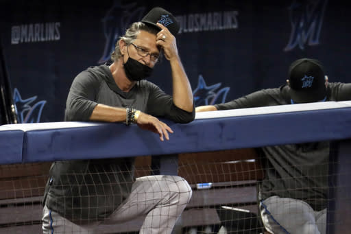 FILE - In this Sunday, July 12, 2020, file photo, Miami Marlins manager Don Mattingly watches a baseball scrimmage at Marlins Park in Miami. Marlins Park will have a new look for its 2020 season debut Friday, Aug. 14, 2020, thanks to cozier dimensions and a switch to artificial turf. Also, the home team is in first place. (AP Photo/Lynne Sladky, File)