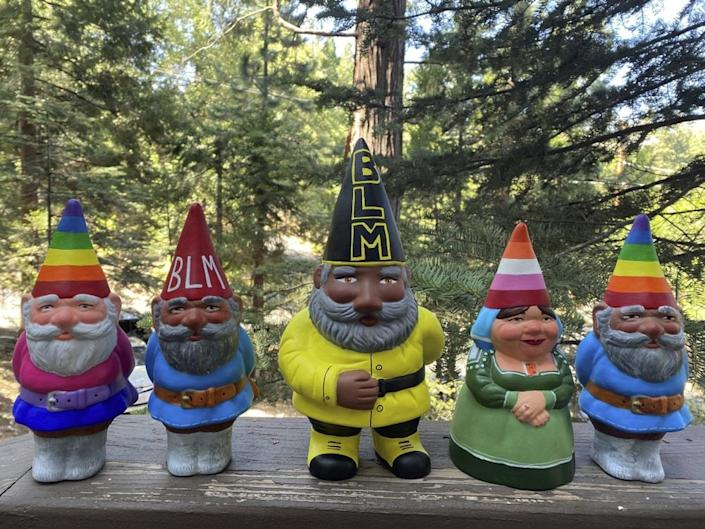 This Sept. 21, 2020, photo provided by Ashleigh Boutelle in Twin Peaks, Calif., shows Black Lives Matter gnomes and gay pride gnomes he painted and is selling online. (Ashleigh Boutelle via AP)