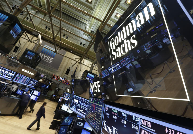 FILE - In this Aug. 15, 2014, file photo, a lighted sign marks the Goldman Sachs trading post on the floor of the New York Stock Exchange. (AP Photo/Richard Drew, File)
