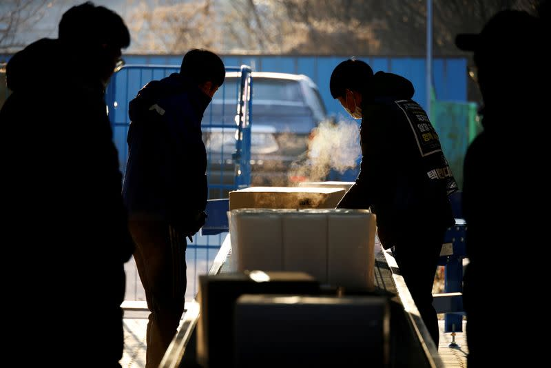 Parcel delivery workers for CJ Logistics, work at its distribution center in Gwangju
