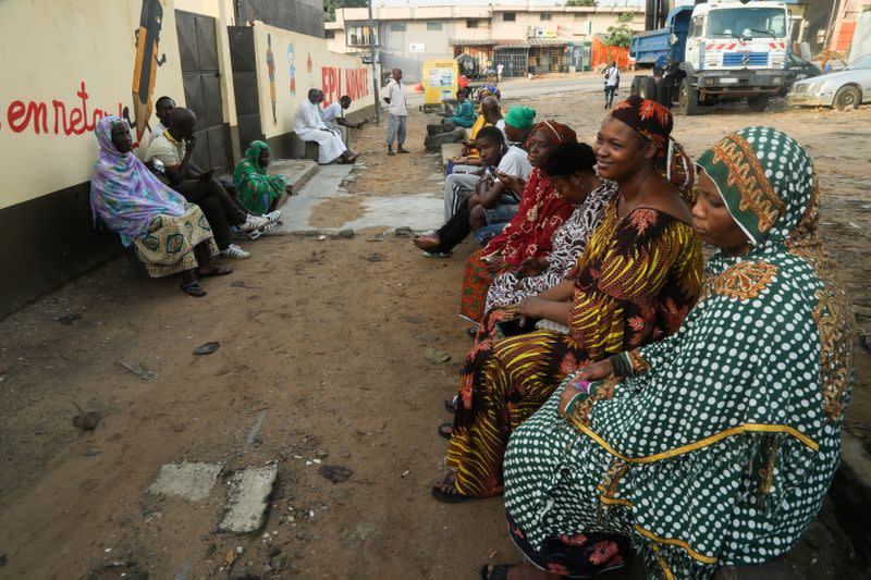 People wait for the opening of a polling office during the presidential election in Abidjan