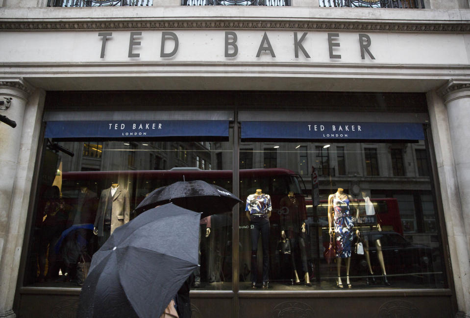 People shelter under umbrellas as they pass a Ted Baker a store in London, Britain October 06, 2015. British designer clothing brand Ted Baker on Tuesday said retail sales were up by just over 20 percent in its first half year, boosted by solid demand at home and a strong performance in North America.   REUTERS/Neil Hall