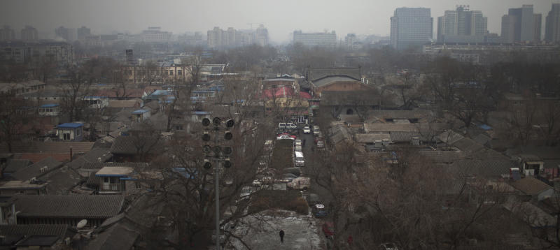 """In this Jan. 15, 2013 photo, a resident, bottom, walks in a """"hutong"""" neighborhood behind the Drum Tower and the Bell Tower in central Beijing, China. The district government wants to demolish these dwellings, move their occupants to bigger apartments farther from the city center and redevelop a square in 18th century Qing Dynasty fashion. (AP Photo/Alexander F. Yuan)"""