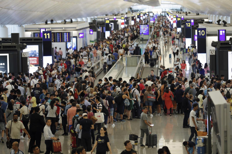 Travelers crowd at the departure hall of the Hong Kong International Airport, Monday, Aug. 12, 2019. One of the world's busiest airports canceled all flights after thousands of Hong Kong pro-democracy protesters crowded into the main terminal Monday afternoon. (AP Photo/Vincent Thian)
