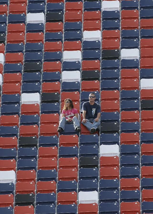 A few fans sit in the stands along the front stretch during practice for Sunday's NASCAR Sprint Cup Series auto race at Talladega Superspeedway in Talladega, Ala., Friday, Oct. 18, 2013.(AP Photo/Dave Martin)