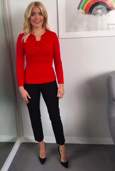 """<p>For her morning television slot, Holly donned a red knot-style <a rel=""""nofollow noopener"""" href=""""https://thefoldlondon.com/product/belmore-top-carmine-red/"""" target=""""_blank"""" data-ylk=""""slk:top"""" class=""""link rapid-noclick-resp"""">top</a> by The Fold and finished the look with <a rel=""""nofollow noopener"""" href=""""https://www.houseoffraser.co.uk/women/jigsaw-bi-stretch-cigarette-trouser/d798290.pd"""" target=""""_blank"""" data-ylk=""""slk:Jigsaw"""" class=""""link rapid-noclick-resp"""">Jigsaw</a> cigarette trousers and heels from <a rel=""""nofollow noopener"""" href=""""https://www.office.co.uk/view/product/office_catalog/2,37/2419600079060?gclid=EAIaIQobChMI4dWhpfP-1gIVQ5UbCh2b9AGLEAQYASABEgJ3XPD_BwE&P36=A1B2CZ&utm_source=AffiliateWindow&utm_medium=Affiliate&utm_campaign=http%3A%2F%2Fwww%2Estandard%2Eco%2Euk%2F&AFF=BU222025"""" target=""""_blank"""" data-ylk=""""slk:Office"""" class=""""link rapid-noclick-resp"""">Office</a>. </p>"""