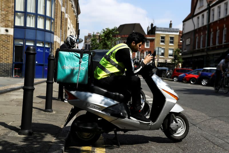 FILE PHOTO: A Deliveroo scooter driver takes a break between deliveries in London